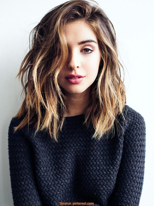 shoulder-length deep side part hairstyle and golden brown hair color